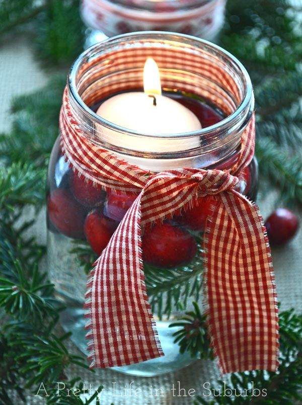 Simple & Lovely Holiday Centerpiece Ideas // mason jars, fresh greens & cranberries, floating candles, ribbon via A Pretty Live in the Suburbs #decor #Christmas