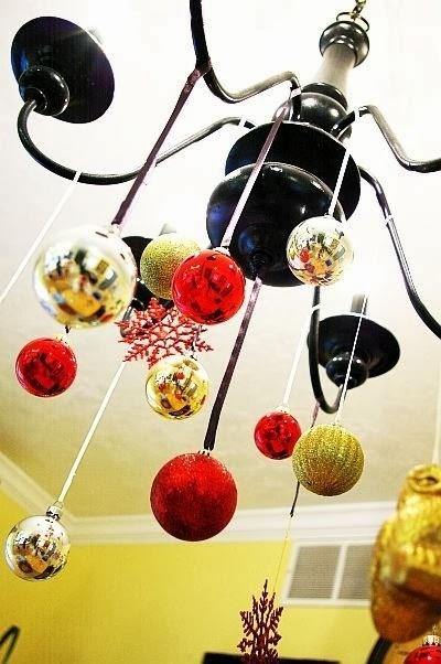Κρεμάστε στολίδια από ένα φωτιστικό για να το μετατρέψουν σε έναν πολυέλαιο Χριστούγεννα.