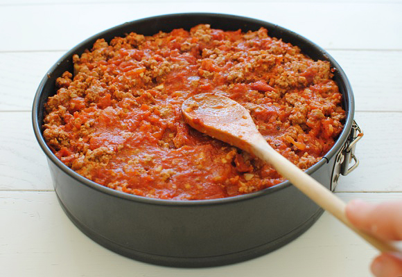 Pour the meat sauce over the top, pressing into ends of noodles.