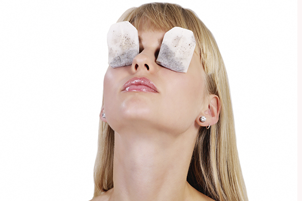 Young woman tea bag therapy for tired or puffy eyes
