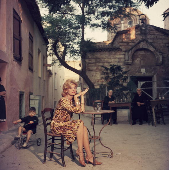 1961:  Greek actress Melina Mercouri (1925 - 1994) sitting at a street cafe in Athens.  (Photo by Slim Aarons/Getty Images)