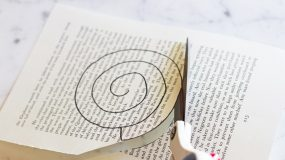 Κόβει μια σελίδα από ένα παλιό βιβλίο.Ο λόγος;Απίστευτη ιδέα για διακόσμηση