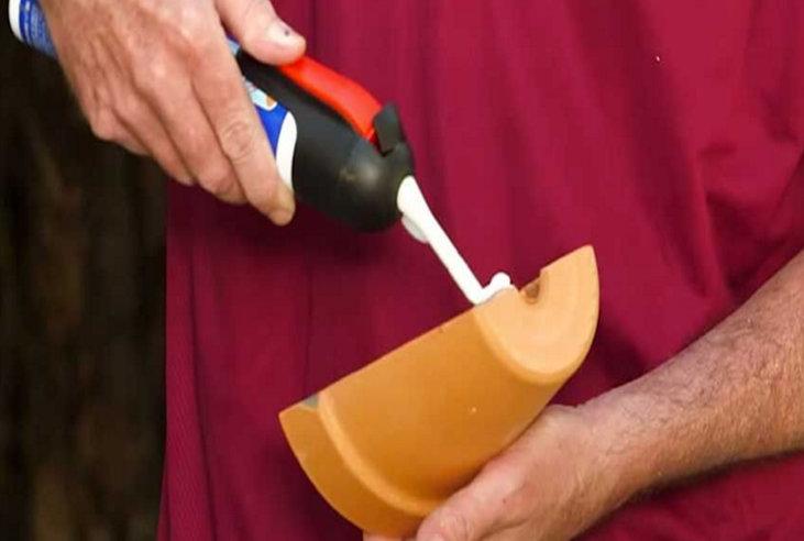 Κόβει  μια πήλινη γλάστρα και  βάζει κόλλα.Το αποτέλεσμα είναι πανέμορφο!