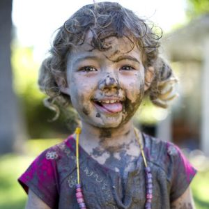 Girl (3-5) covered in mud, smiling