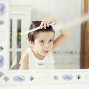 Boy (4-5) combing hair before mirror
