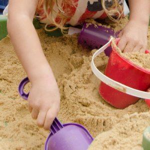 Kids play in a backyard sandbox on a hot summer day.