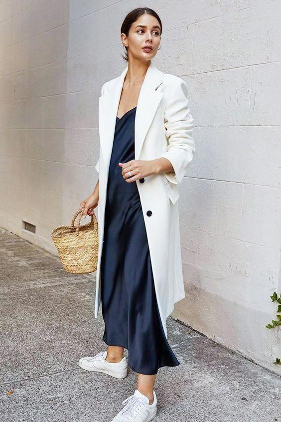 Black & white outfits: μαύρο satin φόρεμα με λευκό παλτό και λευκά sneakers