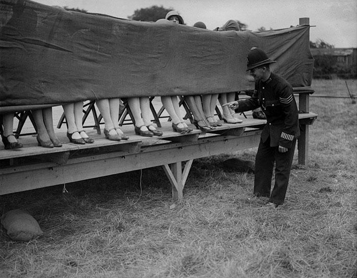 """30 Αδιανόητα πράγματα που οι γυναίκες έκαναν στο παρελθόν για να δείχνουν """"όμορφες"""" : Ένας αστυνομικός κρίνει έναν διαγωνισμό αστραγάλου στο Hounslow, του Λονδίνου, το 1930."""