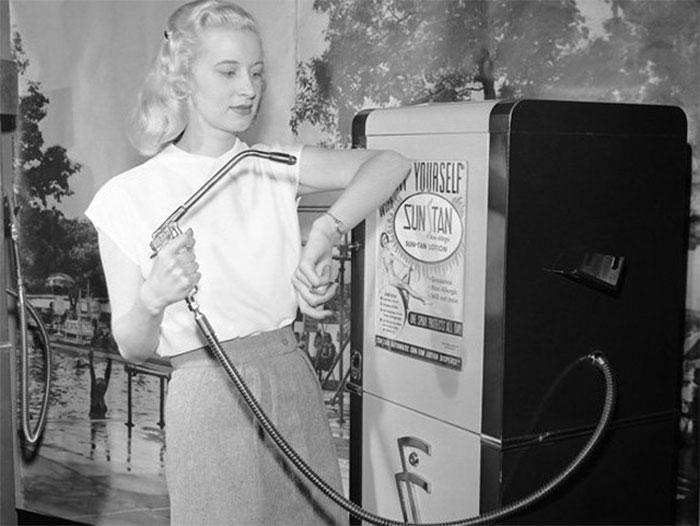 """30 Αδιανόητα πράγματα που οι γυναίκες έκαναν στο παρελθόν για να δείχνουν """"όμορφες"""" : Γυναίκα μαυρίζει χρησιμοποιώντας ένα μηχάνημα αυτόματης πώλησης Suntan, 1949."""