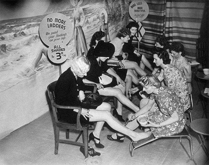 """30 Αδιανόητα πράγματα που οι γυναίκες έκαναν στο παρελθόν για να δείχνουν """"όμορφες"""" : Πελάτισσες ζωγραφίζουν τα πόδια τους σε ένα κατάστημα στο Croydon, Λονδίνο, 1941."""