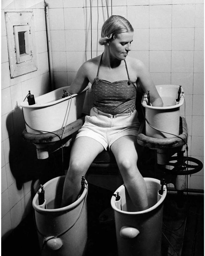 """30 Αδιανόητα πράγματα που οι γυναίκες έκαναν στο παρελθόν για να δείχνουν """"όμορφες"""" : Μια νεαρή γυναίκα κρατά τα χέρια και τα πόδια της σε τέσσερα λουτρά νερού με ηλεκτρικό ρεύμα, για να βελτιώσει την κυκλοφορία του αίματος, γύρω στο 1938."""