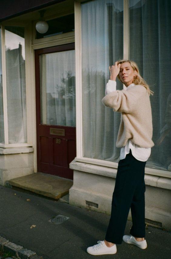 Knitwear outfit: Μπεζ πλεκτό πουλόβερ φορεμένο πάνω από λευκή μπλούζα και μαύρο jean παντελόνι