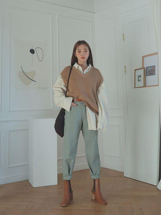 Knitwear outfit: Αμάνικη πλεκτή μπλούζα σε μπεζ αποχρώσεις φορεμένη πάνω από λευκό πουκάμισο με jean παντελόνι και καφέ μποτάκια
