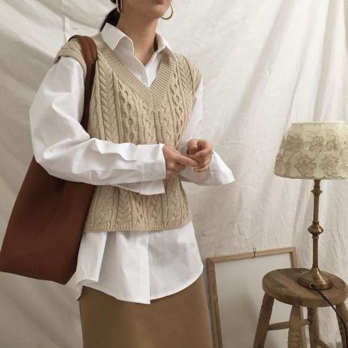 Knitwear outfit: Πλεκτή αμάνικη μπλούζα φορεμένη πάνω από λευκό πουκάμισο με καφέ φούστα και καφέ τσάντα