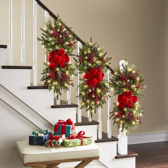 Χριστουγεννιάτικος στολισμός σκάλας με φύλλα δέντρων και κόκκινους φιόγκους
