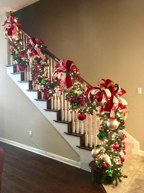 Πράσινη γιρλάντα από φύλλα ελάτου με κόκκινους φιόγκους, κόκκινες χριστουγεννιάτικες μπάλες και φωτάκια led