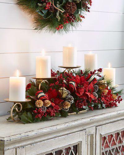 Χριστουγεννιάτικο κηροπήγιο πάνω από το τζάκι με πράσινα ψεύτικα φύλλα πεύκου και κόκκινα διακοσμητικά