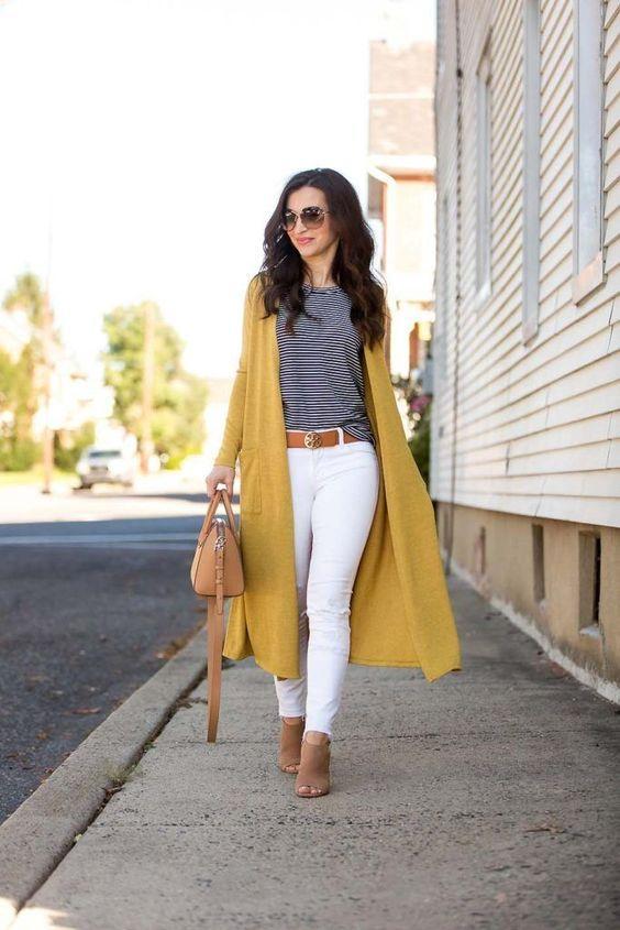 Μουσταρδί μάλλινη ζακέτα με ασπρόμαυρο μπλουζάκι, λευκό παντελόνι και καφέ ζώνη