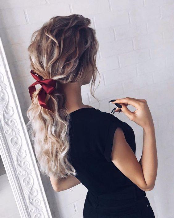 Χτένισμα στα μαλλιά με μπούκλες και κόκκινο υφασμάτινο φιογκάκι